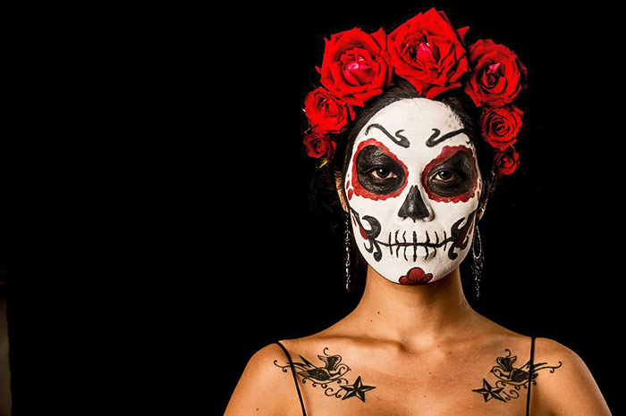 Thai model posing with red roses and face paint