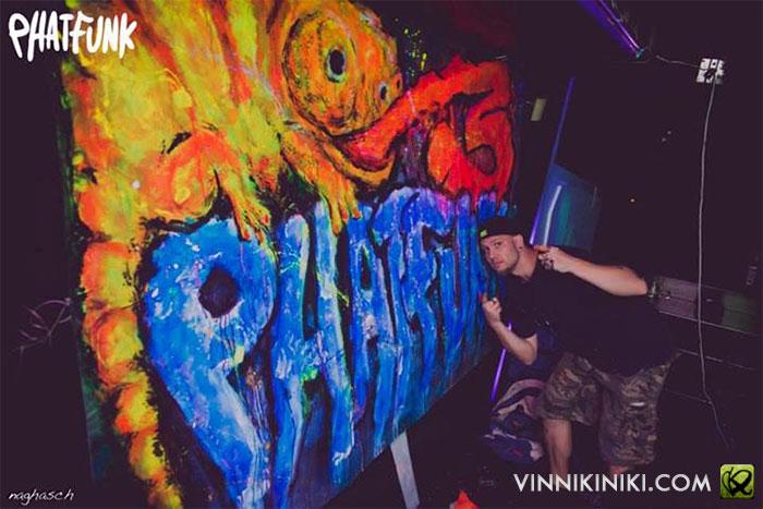 artist posing by UV art